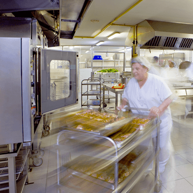 Man Pushing A Cart Full of Bread in A Commercial Kitchen
